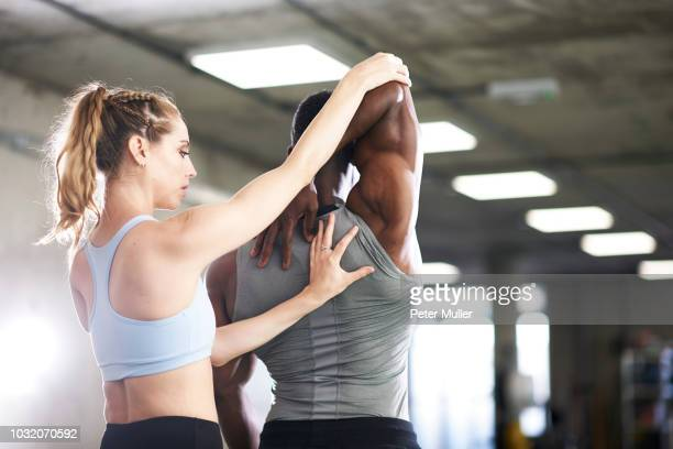 trainer helping man with stretching exercise in gym - peter forte - fotografias e filmes do acervo