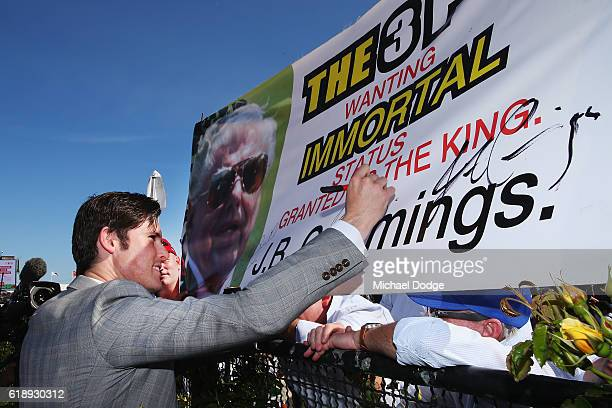 Trainer James Cummings signs a poster after Prized Icon wins race 7 The AAMI Victoria Derby on Derby Day at Flemington Racecourse on October 29 2016...