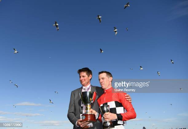 Trainer Jarrod McLean and jockey John Allen who rode Trap For Fools pose with the trophy after winning race 8 the Seppelt Mackinnon Stakes during...