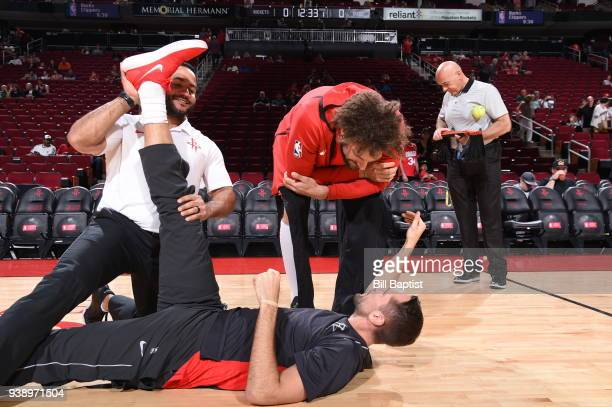 Trainer Javair Gillett stretches Ryan Anderson of the Houston Rockets seen with Robin Lopez of the Chicago Bulls before the game on March 27 2018 at...