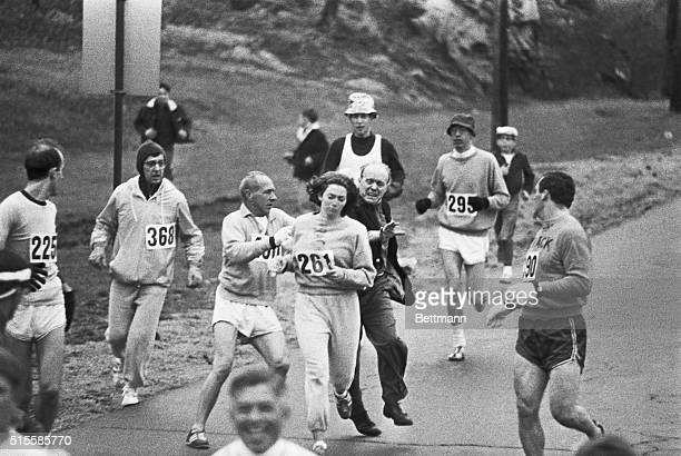 Trainer Jock Semple in street clothes enters the field of runners to try to pull Kathy Switzer out of the race Male runners move in to form a...