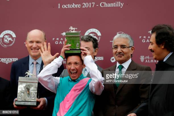 Trainer John Gosden looks on as Jockey Frankie Dettori reacts as he holds the winner's trophy in the 96th Qatar Prix de l'Arc de Triomphe horse race...