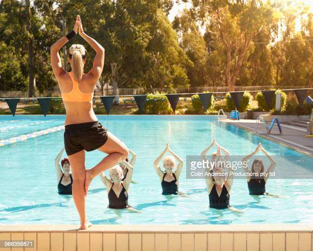 Trainer leading older women in swimming pool fitness class