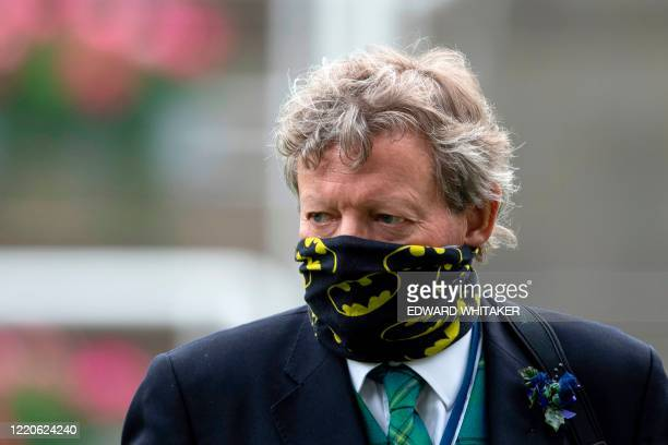 Trainer Mark Johnston wearing PPE , of a face mask or co vering as a precautionary measure against COVID-19, reacts after Jockey William Buick riding...