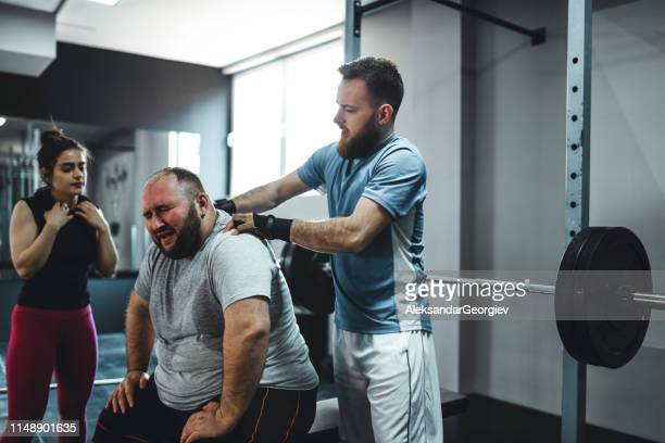 trainer massaging and encouraging overweight middle aged man to train harder - fat massage stock photos and pictures