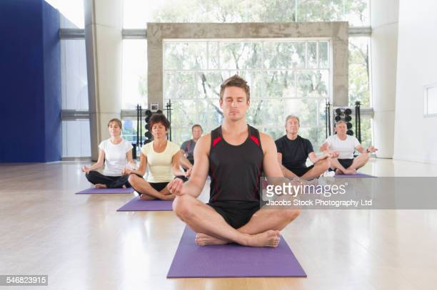 Trainer meditating with class in gym