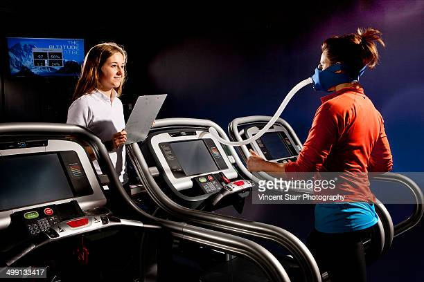 Trainer monitoring mid adult woman with face mask on gym treadmill in altitude centre