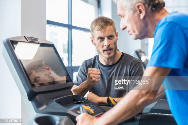 trainer motivating the senior man on treadmill - drug rehab stock pictures, royalty-free photos & images