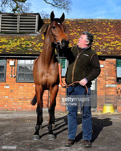 Trainer Paul Nicholls poses with Dodging Bullets at Manor Farm Stables on February 9 2016 in Ditcheat England
