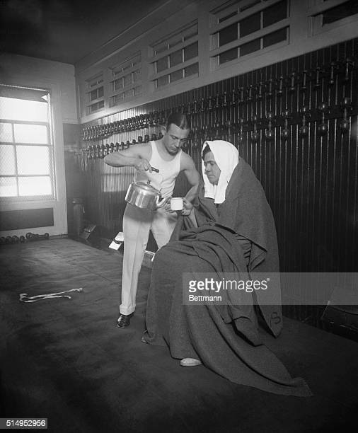 A trainer pours hot water into a mug held by robed baseball champion Babe Ruth as part of the star's training regime