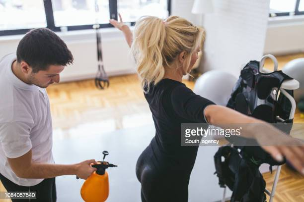 trainer preparing lady for ems training - back to work stock pictures, royalty-free photos & images