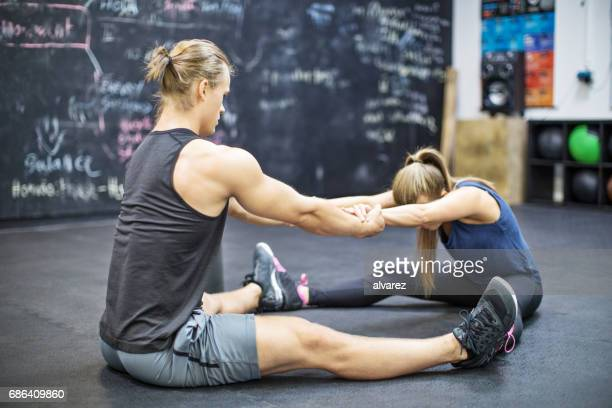 trainer pulling hands of woman at gym - legs apart stock pictures, royalty-free photos & images