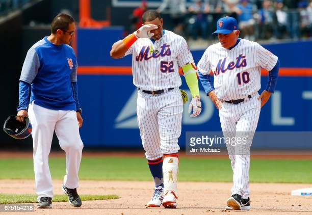 Trainer Ray Ramirez and manager Terry Collins of the New York Mets check on Yoenis Cespedes after an injury against the Atlanta Braves at Citi Field...