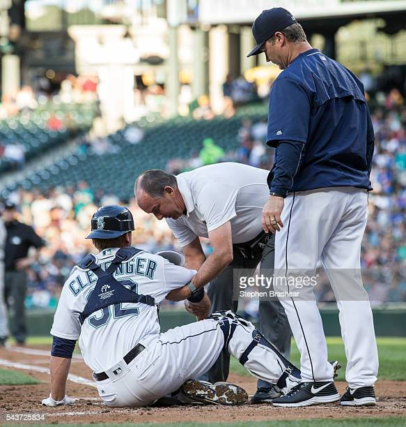 Trainer Rick Griffin and manager Scott Servais of the Seattle Mariners tend to catcher Steve Clevenger during the third inning of a game against the...