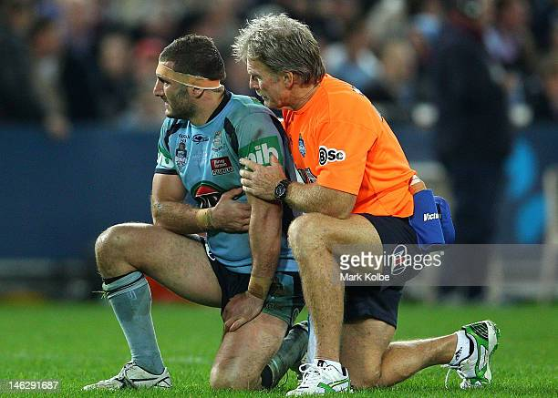 Trainer Ron Palmer attends to Robbie Farah of the Blues during game two of the ARL State of Origin series between the New South Wales Blues and the...