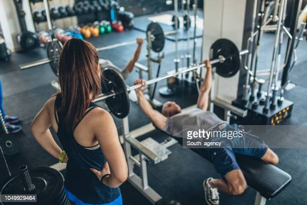 trainer showing exercise to a woman - exercise equipment stock pictures, royalty-free photos & images