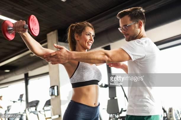 entrenador que ejercicios con pesas - entrenador fotografías e imágenes de stock