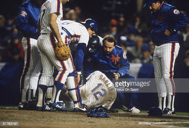 Trainer Steve Garland checks on pitcher Ron Darling of the New York Mets as his teammates gather around during the World Series against the Boston...