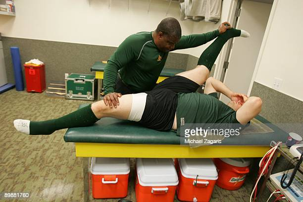 Trainer Steve Sale stretches Landon Powell of the Oakland Athletics in the clubhouse prior to the game against the Colorado Rockies at the Oakland...