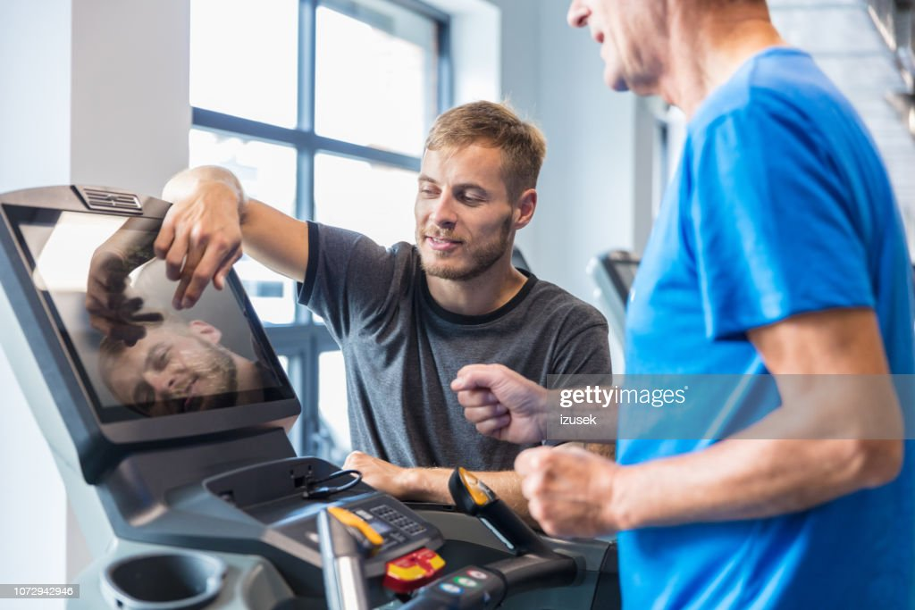 Trainer supervising old man on treadmill : Stock Photo