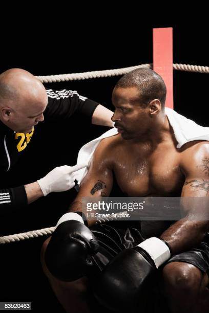 Trainer talking to African boxer in ring