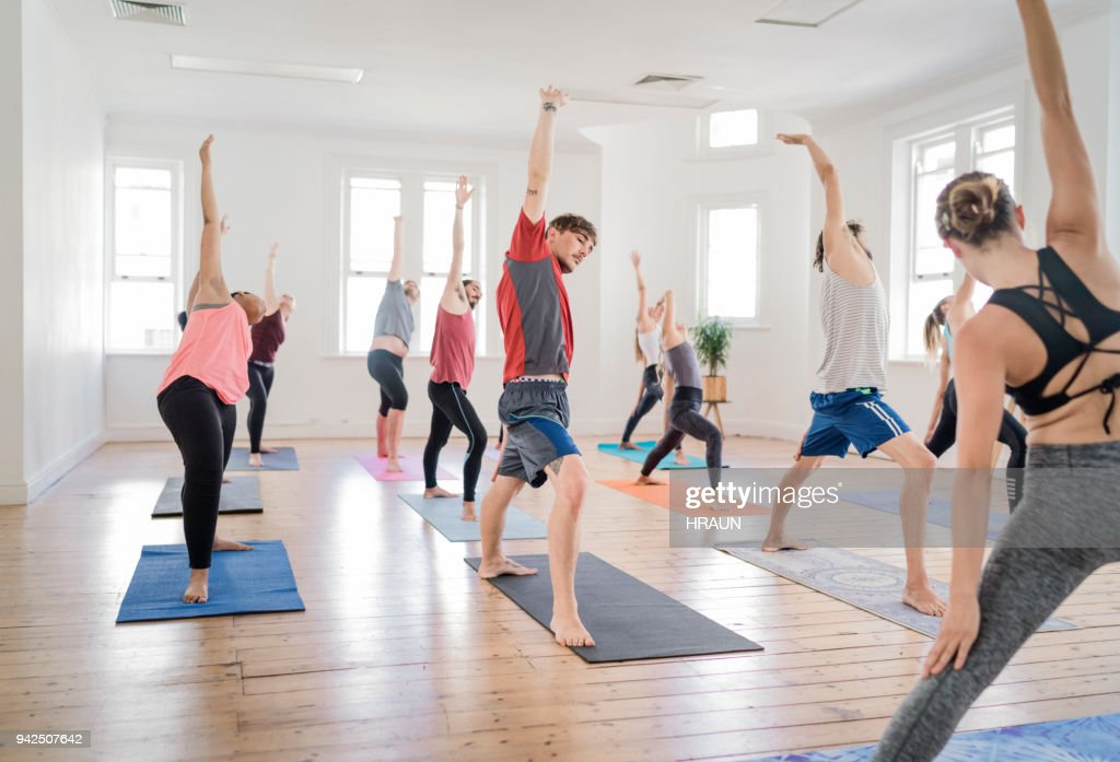 Trainer Teaching Men And Women In Yoga Class Stock Photo
