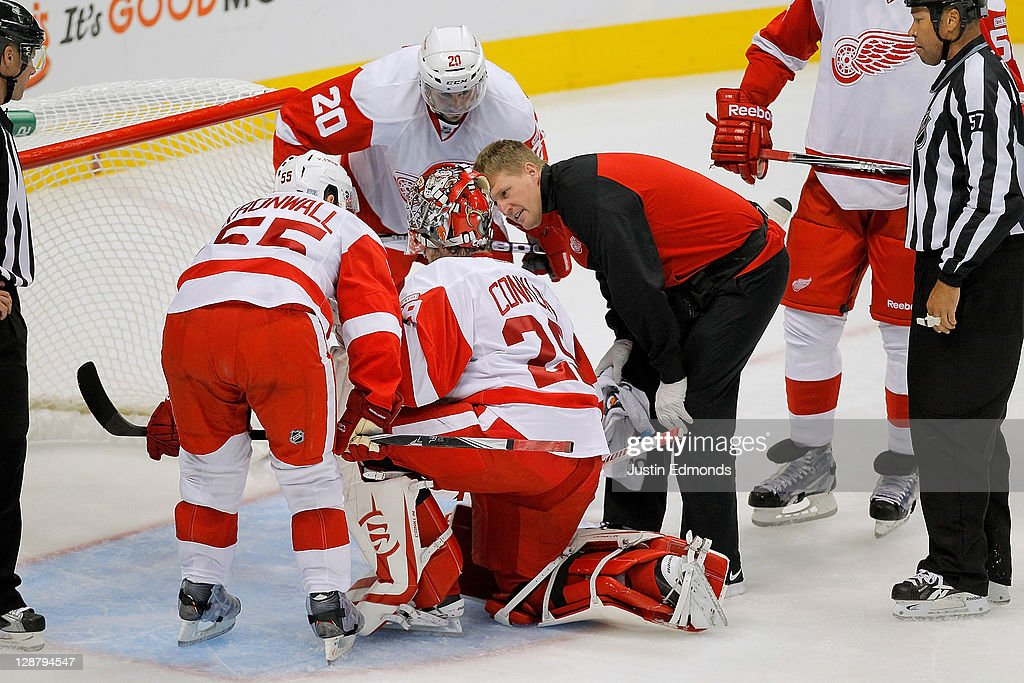 A trainer tends to goalie Ty Conklin #29 of the Detroit Red Wings during the third period against the Colorado Avalanche at Pepsi Center on October 8, 2011 in Denver, Colorado.