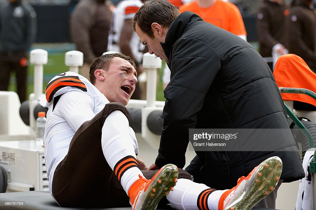 A trainer tends to Johnny Manziel #2 of the Cleveland Browns after he was imjured during their game against the Carolina Panthers at Bank of America Stadium on December 21, 2014 in Charlotte, North Carolina.