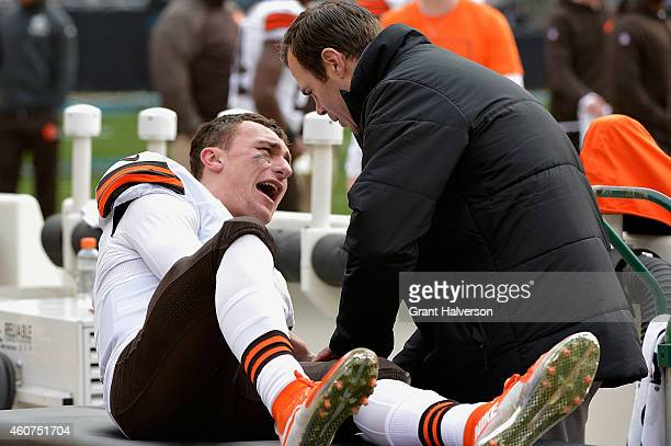 Trainer tends to Johnny Manziel of the Cleveland Browns after he was imjured during their game against the Carolina Panthers at Bank of America...