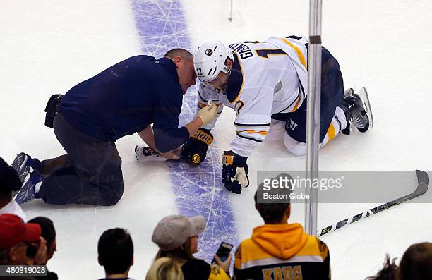 A trainer tends to the Buffalo Sabres' Brian Gionta as he lays on the ice after being hit by the Boston Bruins' Matt Bartkowski during the first...