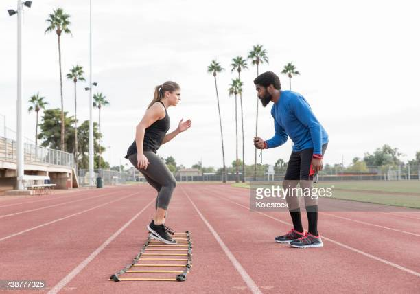 Trainer watching woman running ladder