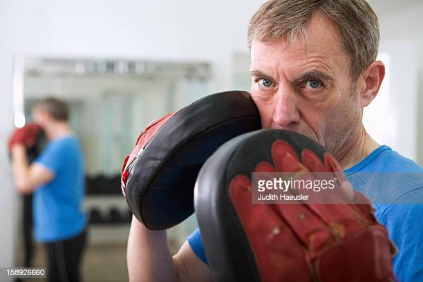 Trainer wearing padded gloves in gym