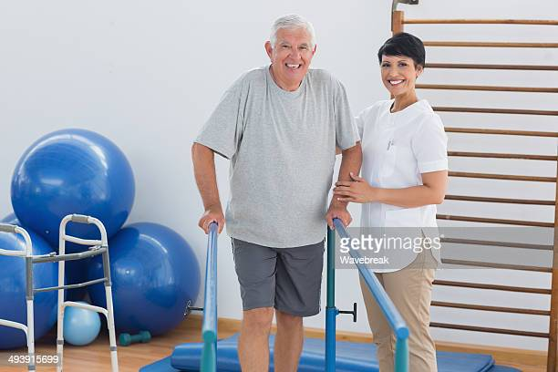 Trainer with senior man walking on parallel bars