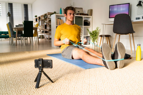 Trainer with tripod stretching rubber while exercising at home