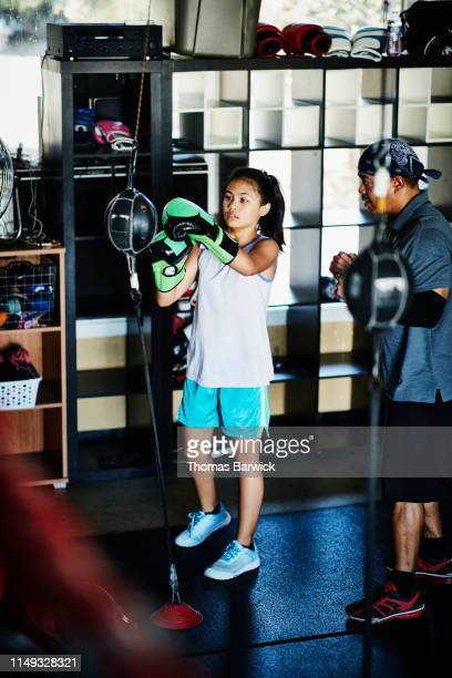 trainer working with young female boxer on double ended bag during workout in gym - boxing shorts stock pictures, royalty-free photos & images