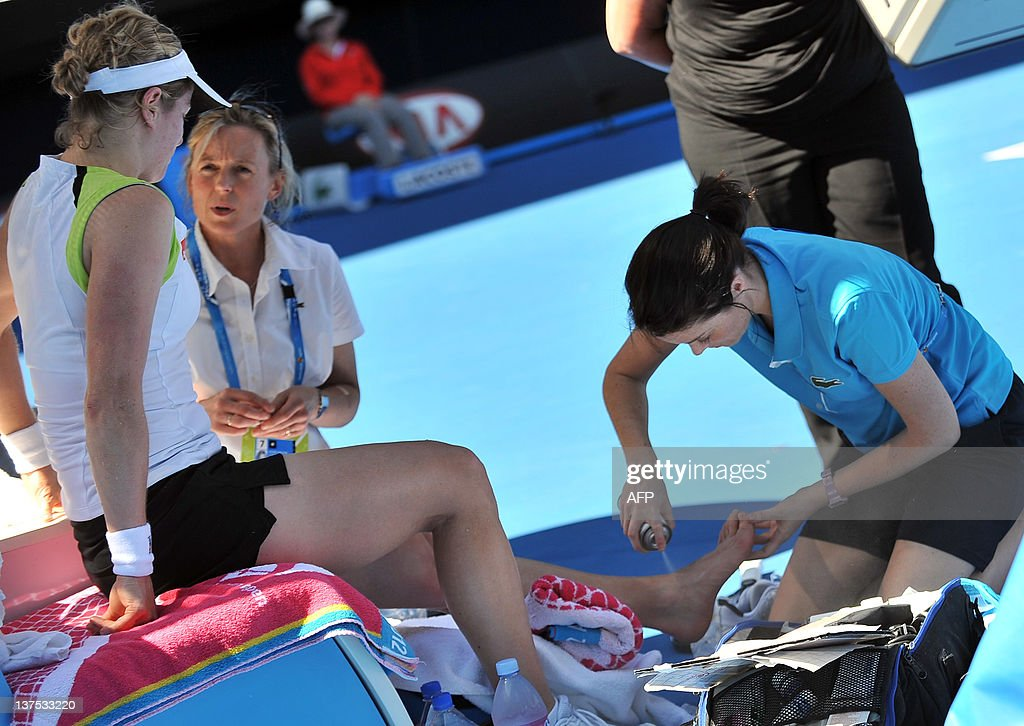 A trainer (R) works on the ankle of Kim : News Photo