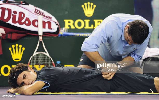 A trainer works on the back of Roger Federer of Switzerland during a break while playing Andy Murray of Britain in their men's singles match on the...