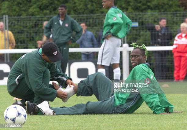 Trainer wraps a bandage on the right ankle of Nigerian defender Taribo West during a practice at Ressons-sur-Matz 15 June. Nigeria will play its...