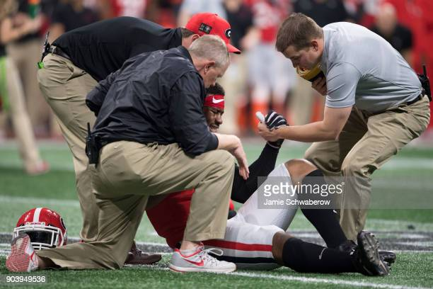 Trainers help David Marshall of the Georgia Bulldogs off the field against the Alabama Crimson Tide during the College Football Playoff National...