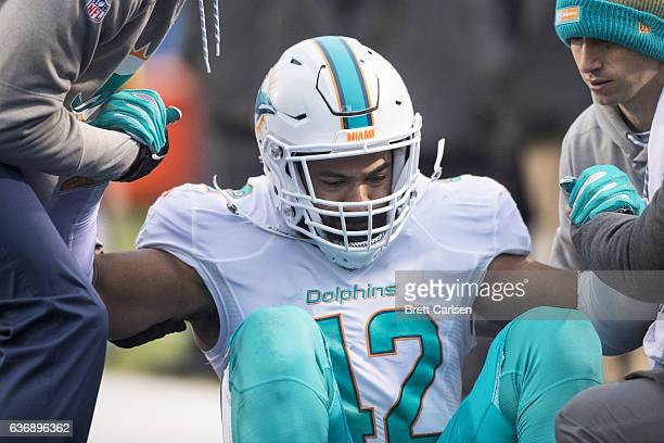 Trainers help Spencer Paysinger of the Miami Dolphins to his feet during the second half against the Buffalo Bills on December 24 2016 at New Era...