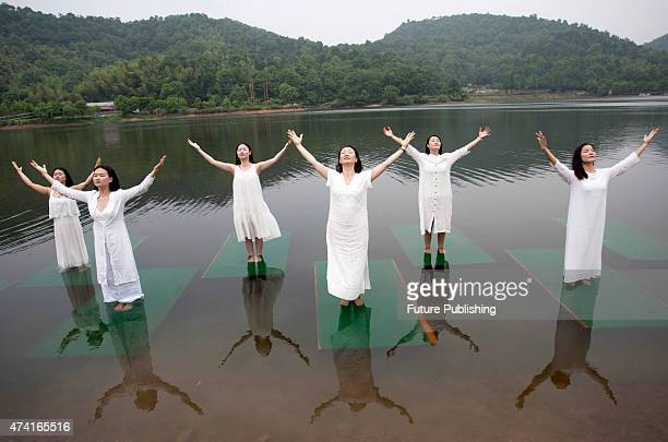 Trainers of a local yoga school perform on bamboo raft in Shiyan Lake on May 20 2015 in Changsha China Feature China / Barcroft Media