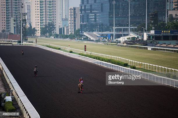 Trainers ride horses during a morning trackwork session on the all-weather dirt track at the Sha Tin Racecourse, operated by Hong Kong Jockey Club,...