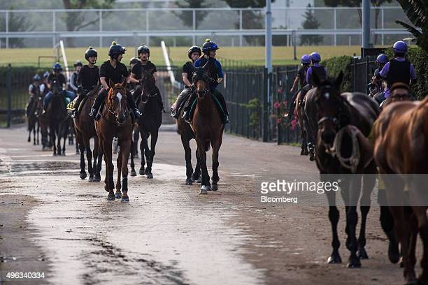 Trainers ride horses through the stable area of the Sha Tin Racecourse, operated by Hong Kong Jockey Club, in Hong Kong, China, on Wednesday, Oct....