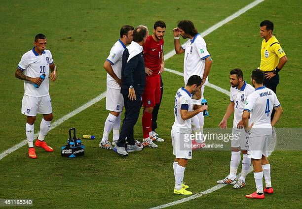 Trainers speak to Orestis Karnezis of Greece after receiving treatment during the 2014 FIFA World Cup Brazil Group C match between Greece and the...