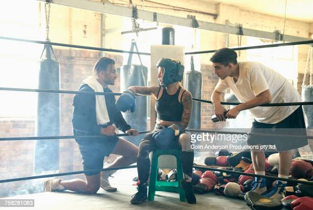 Trainers talking to boxer on stool in boxing ring