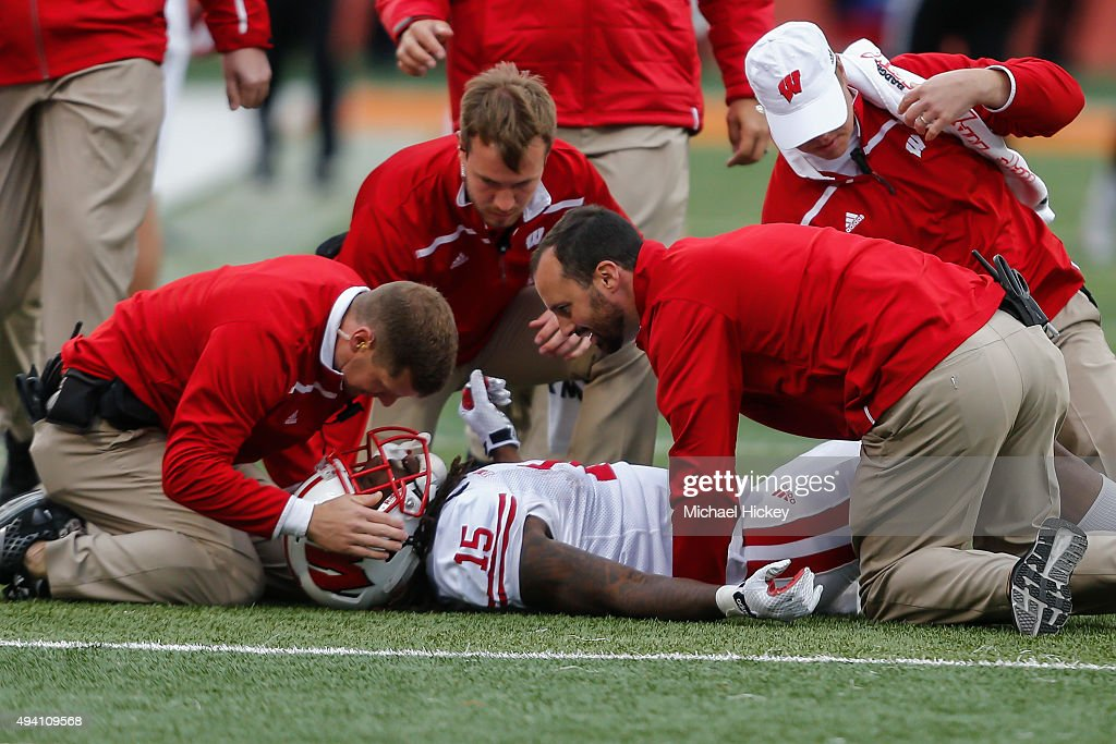 Trainers tend to injured player Robert Wheelwright #15 of the Wisconsin Badgers during the game against the Illinois Fighting Illini at Memorial Stadium on October 24, 2015 in Champaign, Illinois. Wisconsin defeated Illinois 24-13.