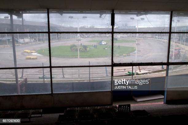Trainers walk their animals around the inside of the track at Wimbledon Stadium ahead of an evening of greyhound racing in south London on March 18...