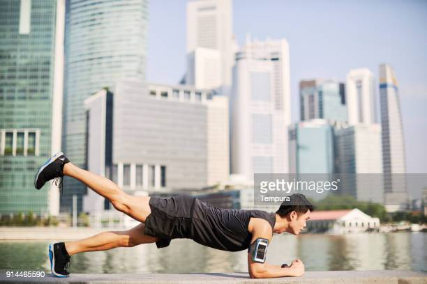 training and running in singapore's marina bay waterfront, asia - plank exercise stock pictures, royalty-free photos & images