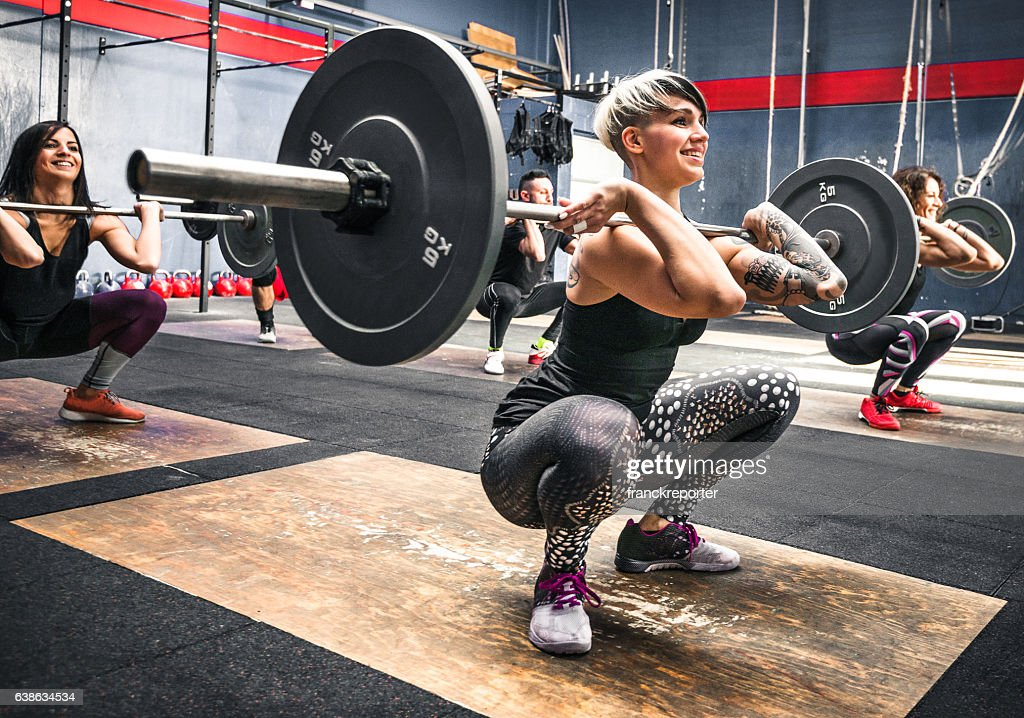 training class doing squat all together : Stock Photo