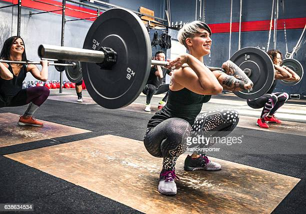 training class doing squat all together - snatch weightlifting stock photos and pictures